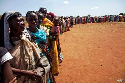 FILE - Internally displaced people, who recently arrived in Wau, South Sudan due to armed clashes in surrounding villages, wait to be registered by the International Organization for Migration and the World Food Program, May 11, 2016.