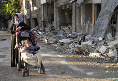A woman stands along a damaged street in the besieged area of Homs January 29, 2014. Efforts to get food and medical aid into Homs have become a test case on whether peace talks in Switzerland can produce any practical results almost three years into...