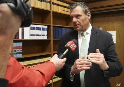 FILE - Former Kansas Secretary of State Kris Kobach answers questions from reporters in Topeka, Kansas, Nov. 30, 2018.