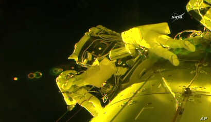 In this image made from video provided by NASA, U.S. astronauts Shane Kimbrough, left, and Peggy Whitson install a shield on a relocated docking port outside the International Space Station, March 30, 2017. An important piece of micrometeorite shield...