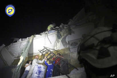 In this photo released early Monday, Oct. 17, 2016 and provided by the Syrian Civil Defense group known as the White Helmets, rescue workers try to remove a boy stuck in the debris of a building in the neighborhood of Qaterji in rebel-held east Alepp...