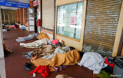 Migrants sleep under blankets in a makeshift camp at the San Giovanni railway station in Como, Italy, Aug. 12, 2016.