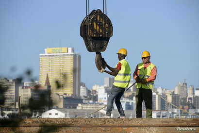 FILE - Construction workers build a bridge against the skyline of Mozambique's capital, Maputo, April 15, 2016.