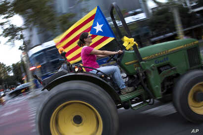 A woman drives a tractor decorated with a pro-independence flag during the Catalan National Day in Barcelona, Spain, Sept. 11, 2018.