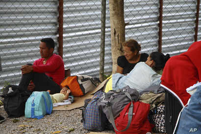Venezuelan migrants rest with their belongings after crossing the border to Pacaraima, in Roraima state, Brazil, Aug. 20, 2018.