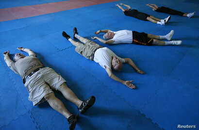 Parkinson's patients Jerry Held (L), Jim Coppula (2nd L) and Dan Cathcart (3rd L) stretch as they begin their workout at Rock Steady Boxing in Costa Mesa, California September 16, 2013. According to the Parkinson's Disease Foundation, research has sh...