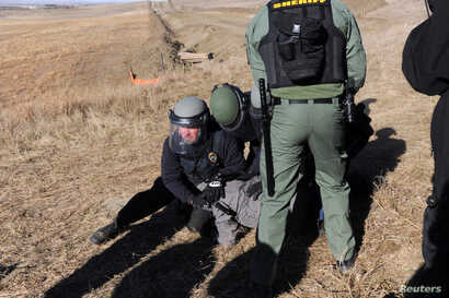 A protester is arrested next to the pipeline route during a protest against the Dakota Access pipeline near the Standing Rock Sioux Reservation in St. Anthony, N.D., Nov. 11, 2016.