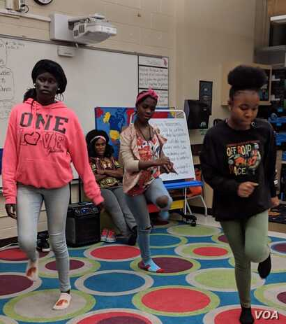 Tricia Gabriel, background, oversees dance practice at the nightly gathering of Genesis Youth Foundation, which helps children of refugees with evening programs to adjust to life in America, in Des Moines, Iowa, Jan. 28, 2019.