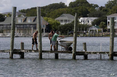 From left, Josh Clappsy, Blake Price, and JB Phillips remove boards from a dock in hopes to save it from rising waters in Swansboro, North Carolina, Sept. 11, 2018.