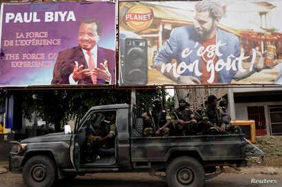 Cameroonian elite Rapid Intervention Battalion (BIR) members sit on their military vehicle under a plazard (L) of Cameroon President Paul Biya, who is running for re-election scheduled for Oct. 7, during a patrol in the south west city of Buea, Camer...