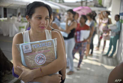 A pregnant woman holds a mosquito net in Cali, Colombia, Feb. 10, 2016. The  Colombian Health Ministry began delivering mosquito nets for free to pregnant women to prevent the infection by Zika virus, vectored by the Aedes aegypti mosquito.