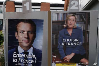 Election campaign posters for French centrist presidential candidate Emmanuel Macron and far-right candidate Marine Le Pen are posted in front of the polling station where Marine Le Pen will vote in Henin Beaumont, northern France, May 6, 2017.