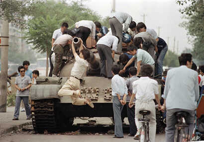 FILE - A young man swings on the barrel of a disabled tank on the streets of Beijing, June 9, 1989, after soldiers crack down on a student-led pro-democracy protest. China's bloody 1989 military crackdown on the Tiananmen Square pro-democracy protest...