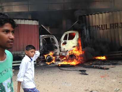 Indian youth walk past as two trucks that came from the neighboring Tamil Nadu state go up in flames during violence in Bangalore, Karnataka state, Sept. 12, 2016.