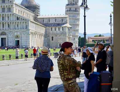 Female soldier standing guard at the Leaning Tower of Pisa, the 14th century bell tower, and its cathedral. Automatic bollards on the access roads to the cathedral square can be raised at a flick of a switch.