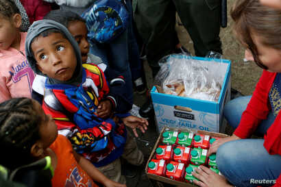 Venezuelan migrant children line up to receive food at a makeshift camp near the transport terminal in Bogota, Colombia, Sept. 5, 2018.