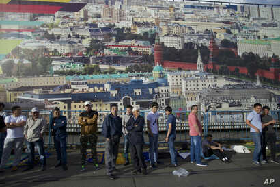 FILE - Muslim men, mostly migrant laborers from Central Asian countries, stand next to a fence decorated with a picture of Moscow's Kremlin in Russia, July 5, 2016.