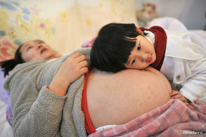 FILE - Li Yan (L), pregnant with her second child, lies on a bed as her daughter places her head on her mother's stomach in Hefei, Anhui province, Feb. 20, 2014.
