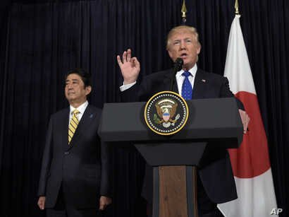 President Donald Trump speaks as Japanese Prime Minister Shinzo Abe listens as they both made statements about North Korea at Mar-a-Lago in Palm Beach, Fla., Feb. 11, 2017.