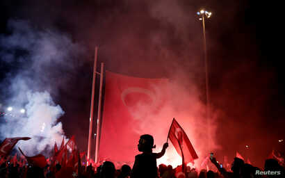 A young boy waves a Turkish national flag as supporters of Turkish President Tayyip Erdogan gather during a pro-government demonstration on Taksim square in Istanbul, Turkey, July 18, 2016.
