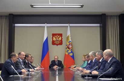 Russian President Vladimir Putin (C) chairs a meeting with members of the Security Council at the Novo-Ogaryovo state residence outside Moscow, Russia, September 29, 2015.