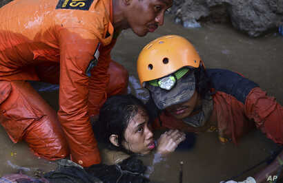 Rescuers evacuate an earthquake survivor by a damaged house following earthquakes and tsunami in Palu, Central Sulawesi, Indonesia, Sunday, Sept. 30, 2018.