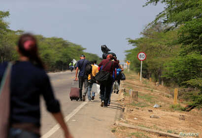 Venezuelans walk on a highway after crossing the border between Venezuela and Colombia, in Paraguachon, Colombia, February 16, 2018.