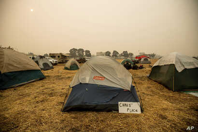 A sign hangs beside a tent at a makeshift shelter for evacuees of the Camp Fire in Chico, Calif., Nov. 14, 2018.