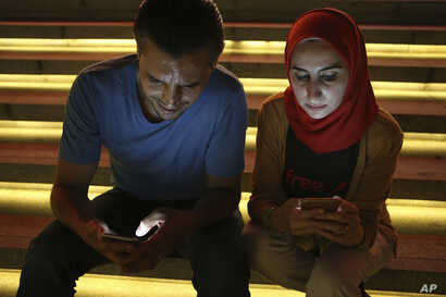 FILE - In this Aug. 1, 2016 file photo, Bahr Abdul Razzak, left, and his wife Noura Al-Ameer, use their smartphones in Istanbul.
