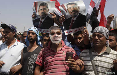 A supporter of deposed Egyptian President Mohamed Morsi wears a mask depicting Mursi as protesters chant slogans outside the Republican Guard headquarters in Cairo, July 7, 2013.