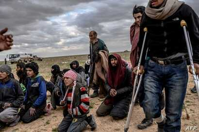 Men and boys suspected of being Islamic State (IS) fighters wait to be searched by members of the Kurdish-led Syrian Democratic Forces (SDF) after leaving the IS group's last holdout of Baghouz, in Syria's northern Deir Ezzor province, Feb. 27, 2019....