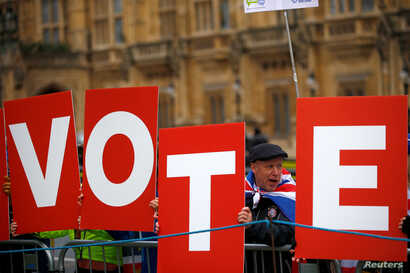 Anti-Brexit demonstrators hold placards outside the Houses of Parliament in London, Britain, Dec. 10, 2018.