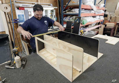 In this July 11, 2018, photo, a worker assembles interior boat cabinets in Orlando, Florida, which has no state income tax.