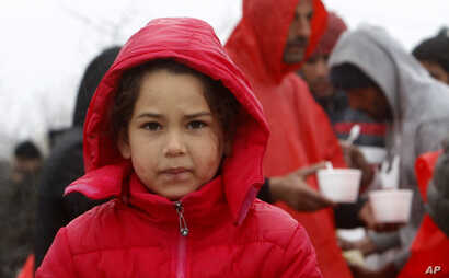 A refugee girl walks in the rain at an improvised camp on the border line between Macedonia and Serbia near northern Macedonian village of Tabanovce, March 10, 2016.