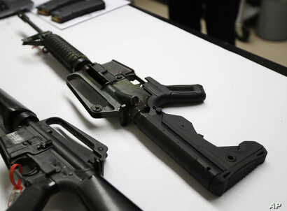 In this Jan. 11, 2018 photo, a semi-automatic rifle at right that has been fitted with a so-called bump stock device to make it fire faster sits on a table at the Washington State Patrol crime laboratory in Seattle.