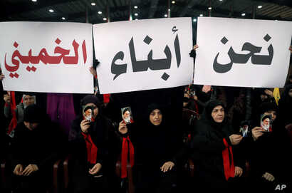 """FILE - Hezbollah supporters hold up Arabic placards that read, """"We are the sons of Khomeini,"""" during a rally to commemorate the 40th anniversary of Iran's Islamic Revolution, in southern Beirut, Feb. 6, 2019."""