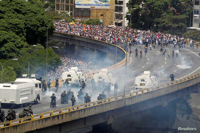 """Demonstrators clash with riot police during the so-called """"mother of all marches"""" against Venezuela's President Nicolas Maduro in Caracas, Venezuela, April 19, 2017."""