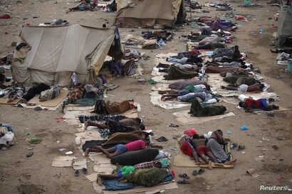 Ethiopian migrants sleep out in the open near a transit centre where they wait to be repatriated, in the western Yemeni town of Haradh, on the border with Saudi Arabia, May 21, 2013.