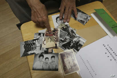 FILE - Lee Soo-nam, 76, explains the photos showing his family members during an interview at his home in Seoul, South Korea, Aug. 17, 2018. Lee is among about 200 war-separated South Koreans and their family members who are crossing into North Korea...