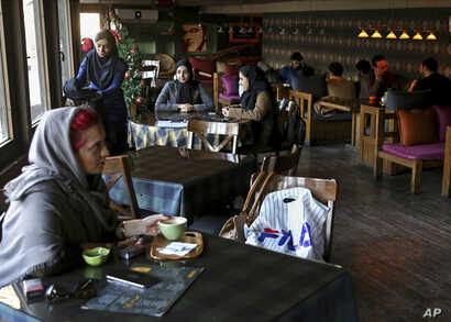 Young people spend their time at a cafe in downtown Tehran, Iran, Jan. 3, 2018. Tens of thousands of Iranians took part in pro-government demonstrations in several cities across the country in the last several days, Iranian state media reported, a mo...