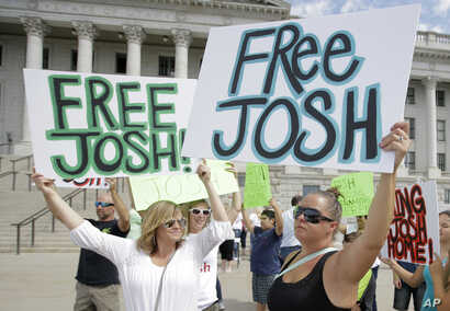 FILE - People show their support for Joshua Holt, an American jailed in Venezuela, during a rally at the Utah State Capitol, in Salt Lake City, July 30, 2016.