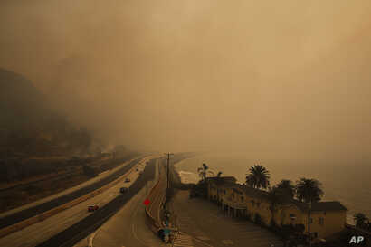 Traffic moves along the 101 Freeway as smoke from a wildfire fills the air in Ventura, California, Dec. 7, 2017.