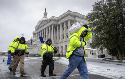 Workmen clear snow on Capitol Hill in Washington, March, 14, 2017.
