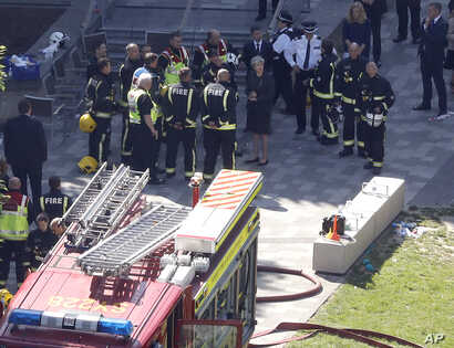 Britain's Prime Minister Theresa May, center, speaks with firefighters after arriving at Grenfield Tower in London, June 15, 2017, following a deadly fire in the apartment block.