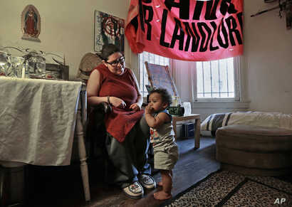 FILE - Franki Velez looks at her son Ashoka Little, 1, in their home in Oakland, California, Feb. 17, 2017.