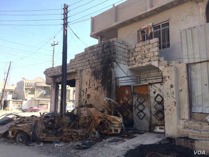 Neighbors say this small shop was occupied by IS militants and hit by an airstrike in January. They say the blood on the wall belongs to a family fleeing in the struck car on Feb. 7, 2017, in Mosul, Iraq. (H. Murdock/VOA)