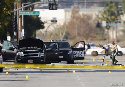 A police officer picks up a weapon from the scene of the investigation around the area of the SUV vehicle where two suspects were shot by police following a mass shooting in San Bernardino, California, Dec. 3, 2015.