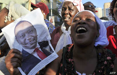 Supporters of Kenya's President Uhuru Kenyatta, celebrate in the streets of Nairobi following the International Criminal Court's ruling to drop crimes against humanity charges against him, at the ICC courts at the Hague, Dec. 5, 2014.
