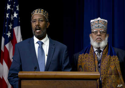 FILE - Abdisalam Adam a public school teacher and imam from St. Paul, Minn. (left) and Imam Sheikh Sa'ad Musse Roble, of the World Peace Organization in Minneapolis, participate in the White House Summit on Countering Violent Extremism, Feb. 18, 2015...