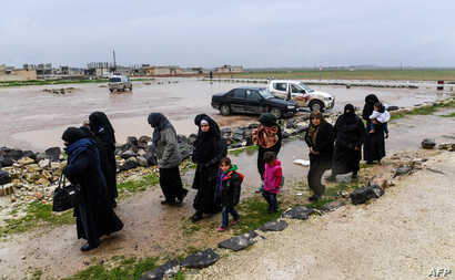 Syrian civilians cross from rebel-held areas in Idlib province into regime-held territories on December 27, 2018, through the Abu Duhur crossing.